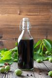 A bottle of homemade nut liqueur with unripe walnuts royalty free stock photos