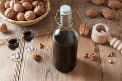 A bottle of homemade nut liqueur with walnuts stock image