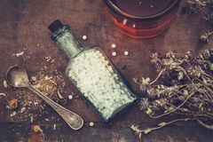 Bottle of homeopathic globules, bunch of dry healthy herbs and glass of tincture or healthy tea. Royalty Free Stock Photography