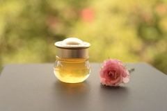 Bottle of honey with pink rose Royalty Free Stock Photography