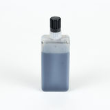 Bottle of ink. Closeup of a jar of black liquid. Isolated on a w Royalty Free Stock Photo