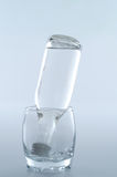 Bottle inside glass Stock Images