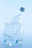 Bottle inside glass Stock Photography