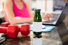 Bottle Of Juice With Dumbbells. In Front Of Businesswoman Using Laptop stock image