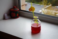 A bottle with juice near the window stock images