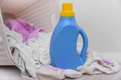 Bottle of laundry detergent in the basket with dirty baby clothes. Bottle of laundry detergent in a basket of dirty baby clothes. Close-up stock photography