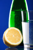 Bottle with lemon. Green bottle with lemon and glass Stock Photo