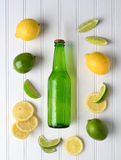 Bottle of Lemon Lime Soda. High angle shot of a bottle of lemon lime soda surrounded by fresh cut and whole lemons and limes. Vertical format stock photo