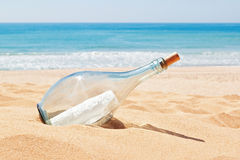 A bottle with a letter of distress on the beach. Summer Stock Photo