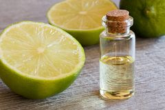 A bottle of lime essential oil with fresh limes stock image