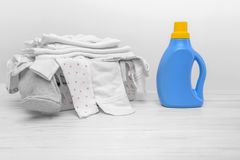 Bottle with liquid detergent against the background of the basket with baby clothes. stock photos