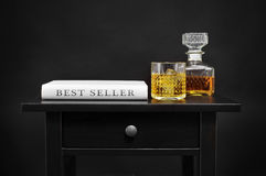 Bottle with liquor and book with the text best seller. A book with the text best seller written in its spine, and a bottle and a lowball glass with liquor on a Stock Photography