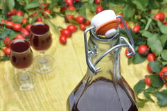 A bottle of liquor, glasses and rosehip fruit Stock Photos