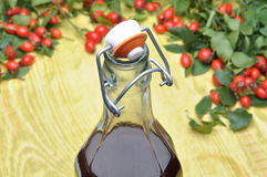 A bottle of liquor and rosehip fruit Stock Photos