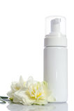 Bottle with  lotion and flowers Royalty Free Stock Photo
