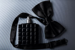 Bottle of male perfume and bow tie. Bottle of male perfume and black bow tie Royalty Free Stock Photos