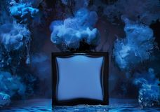The  bottle of man`s perfume in a water wave with clubs of blue paint around the bottle Stock Photography