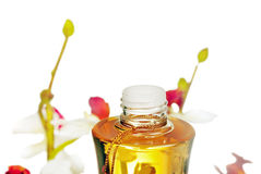 Bottle with massage oil and flowers stock photos