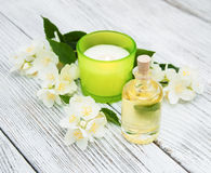 Bottle with massage oil. And jasmine flowers on a table stock photography