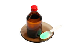 Bottle with a medicine and a spoon. On a black saucer it is isolated on the white Royalty Free Stock Images