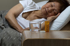 Bottle of medicine and water with senior woman sleeping in backg stock photography