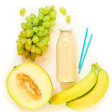 Bottle of melon, grapes, banana juice isolated on white. Glass bottle of melon, grapes, banana juice and ingredients isolated on white background. Top view Royalty Free Stock Images