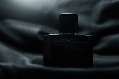 Bottle of men perfume and grey cloth Stock Images
