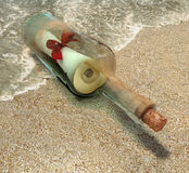 Bottle message. Isolated transparent bottle with message in a red ribbon bow lying at the beach Royalty Free Stock Images