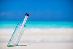 Bottle with a message buried in the white sand Royalty Free Stock Image