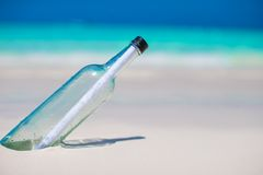 Bottle with a message buried in the white sand Stock Photos