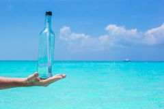 Bottle with a message in the hand background blue Stock Images