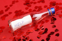 Bottle with message for help on red background with hearts glitters. Stock Photography