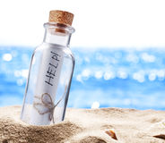 Bottle with a message for help. Sea beach Stock Photos