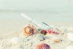 Bottle with a message or letter on the beach near seashell. SOS. Copy space. Royalty Free Stock Photos