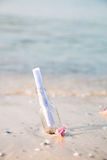 Bottle with a message or letter on the beach. SOS. Copy space. Help. Bottle with a message or letter on the beach near seashell. SOS Stock Photography
