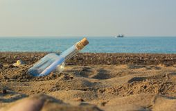 Bottle with a message. Rolled letter inside glass bottle on a beach Stock Photos