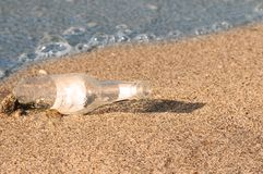 Bottle with message on sand Stock Image
