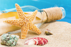 Bottle with message and shells. Vacation concept Stock Photos