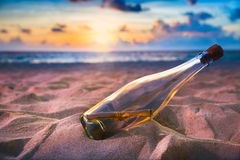 Bottle with a message on a shore Royalty Free Stock Image