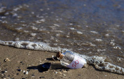 Bottle with a message. Sos message in a bottle isolated on beautiful beach Royalty Free Stock Photo