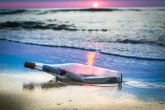 A bottle with a message thrown by the sea. At sunset Royalty Free Stock Photo