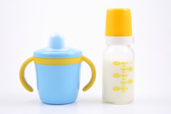Bottle of milk and baby cup Stock Photos