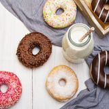 Bottle of milk and colorful donuts with chocolate and icing,. Selective focus Stock Photography