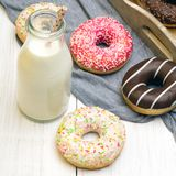 Bottle of milk and colorful donuts with chocolate and icing. Selective focus Stock Photo