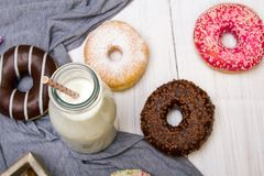 Bottle of milk and colorful donuts with chocolate and icing,. Selective focus Royalty Free Stock Photography