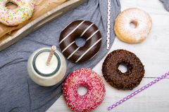 Bottle of milk and colorful donuts with chocolate and icing Stock Images