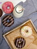 Bottle of milk and colorful donuts with chocolate and icing Stock Photos