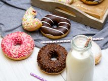 Bottle of milk and colorful donuts with chocolate and icing. Selective focus Royalty Free Stock Image