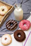 Bottle of milk and colorful donuts with chocolate. And icing, selective focus Royalty Free Stock Images
