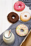 Bottle of milk and colorful donuts with chocolate and icing, Royalty Free Stock Photos